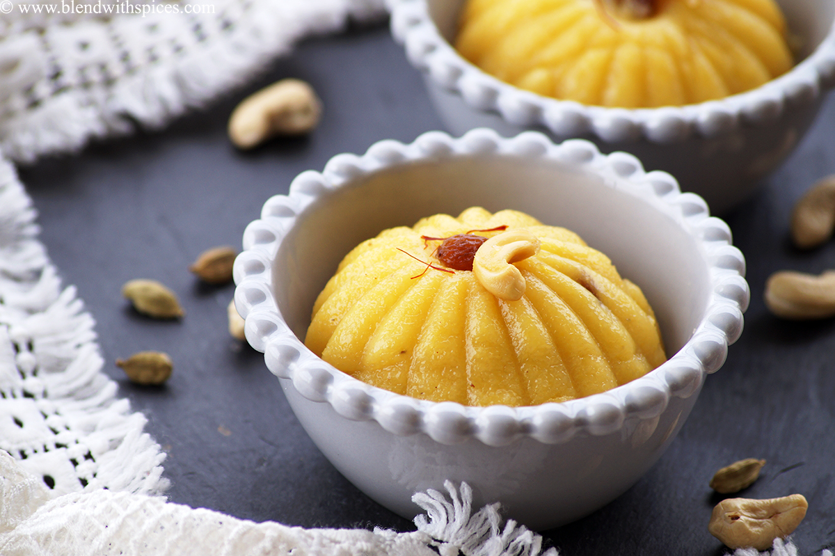 A cardamom infused mango semolina pudding also known as mango sheera served in grey color bowls with cashews and raisins.