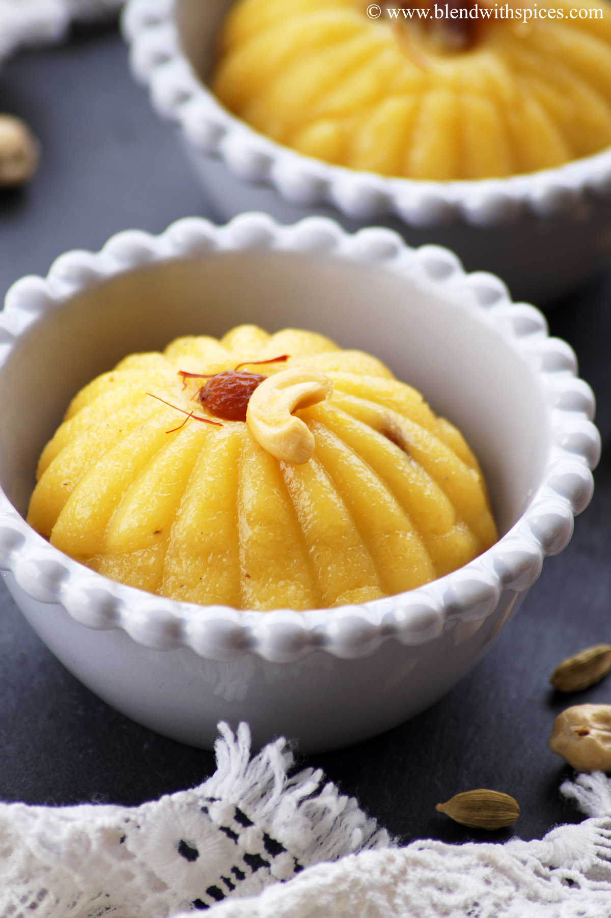 Mango sooji ka halwa served in a grey color bowl topped with fried cashew, raisin and saffron.
