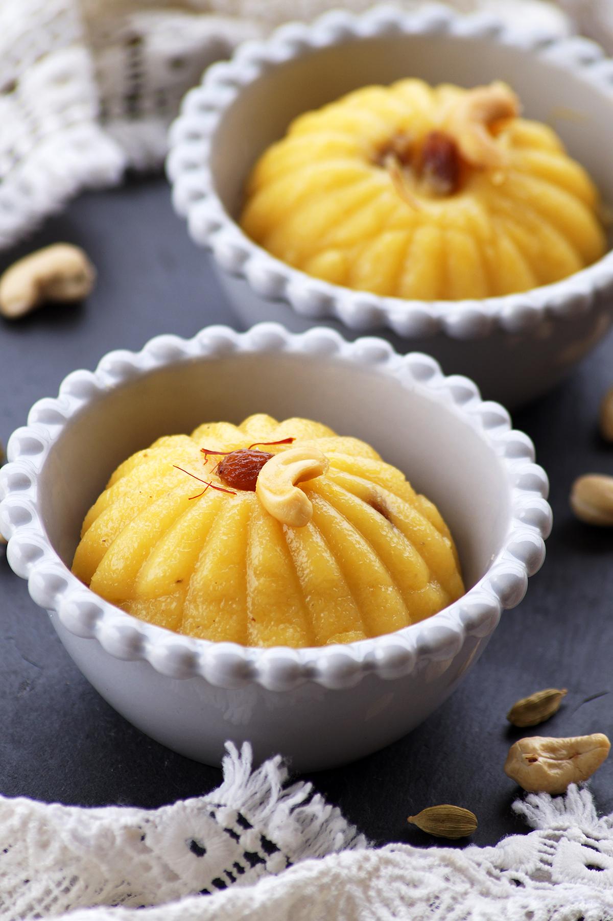 mango kesari or mango semolina pudding topped with saffron, cashews and raisins, served in two bowls.