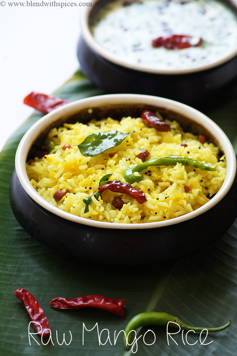 Yellow colored raw mango rice garnished with chillies and curry leaves