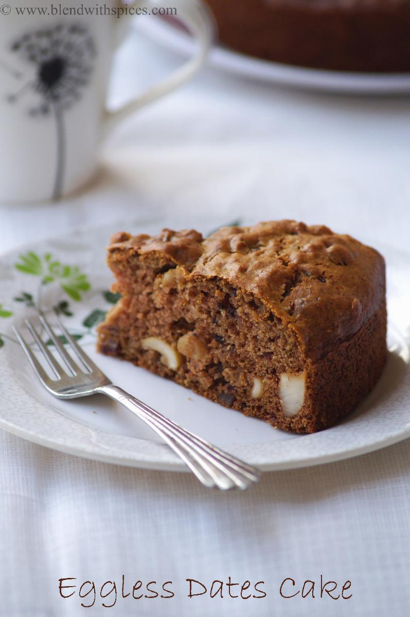 moist and soft date cake slice served on a white plate along with a fork