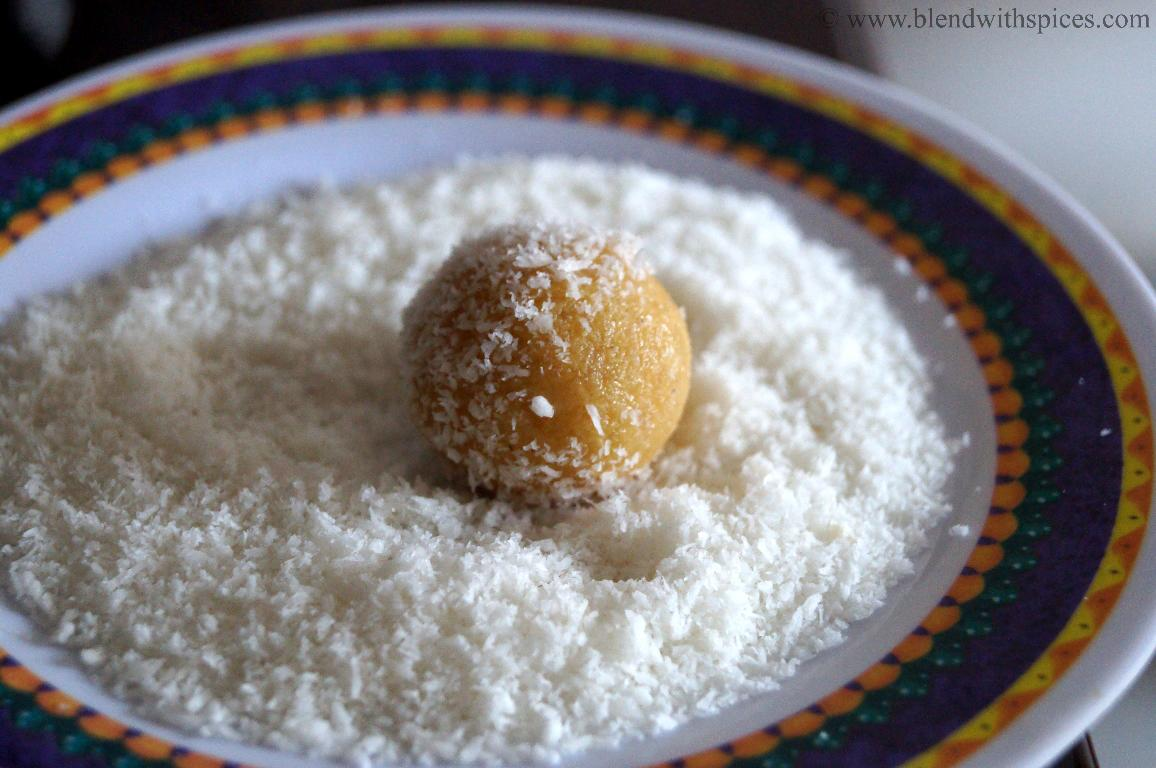rolling the mawa jaggery laddu in coconut