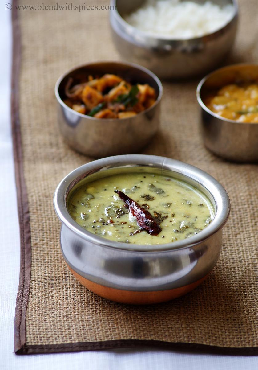 a bowl of ponnaganti majjiga pulusu served along with curry, dal and rice
