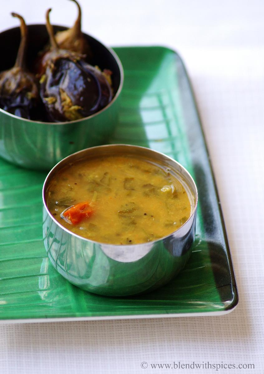 Keerai Sambar served in a steel container along with stuffed brinjal curry