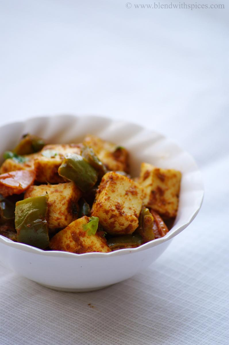a closeup shot of paneer capsicum curry served in a white bowl