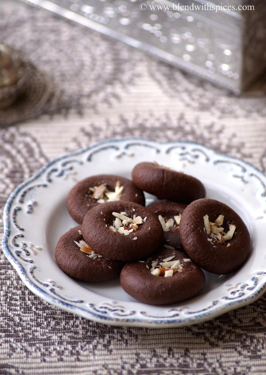Chocolate pedas are decorated with almonds and arranged on a white plate for diwali