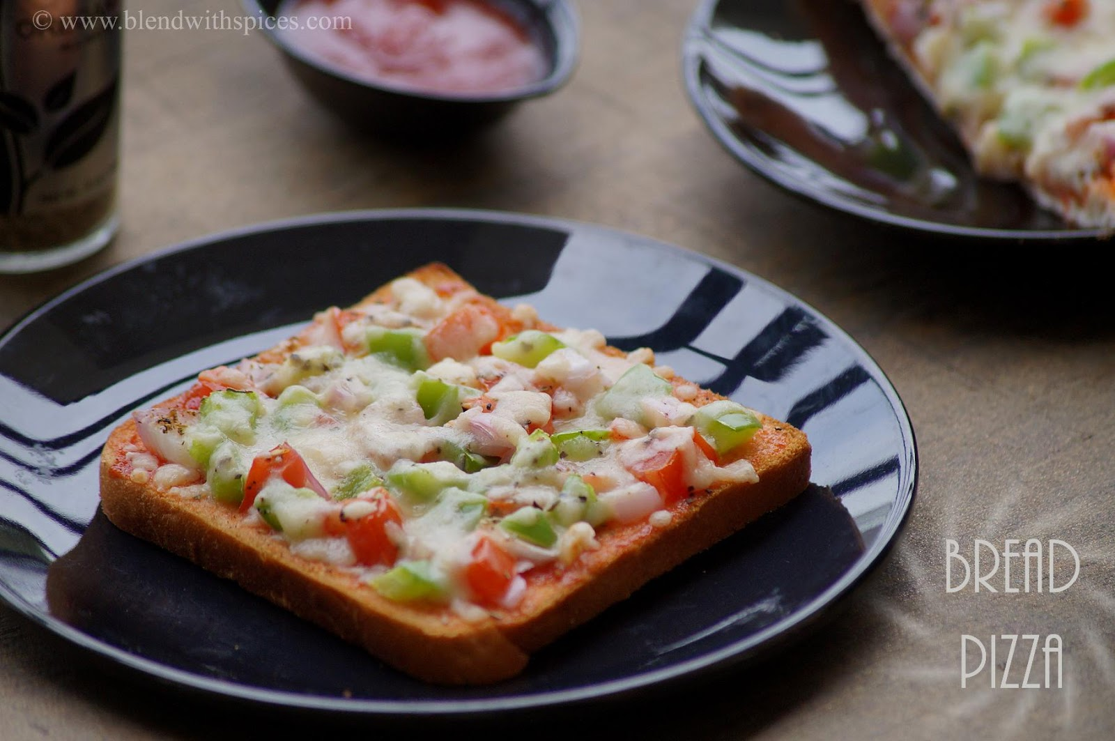 freshly baked bread pizza with capsicum, onion, tomato and mozzarella cheese
