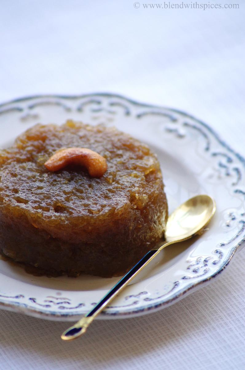 jaggery kasi halwa garnished with fried cashew and served on a white plate with spoon