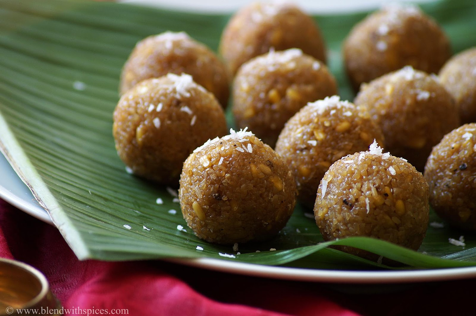 steamed jaggery dumplings garnished with coconut and served on a banana leaf during a festival.