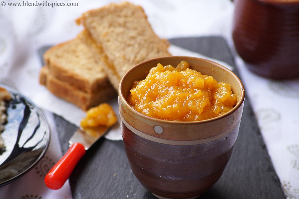 a bowl of homemade persimmon jam served with bread