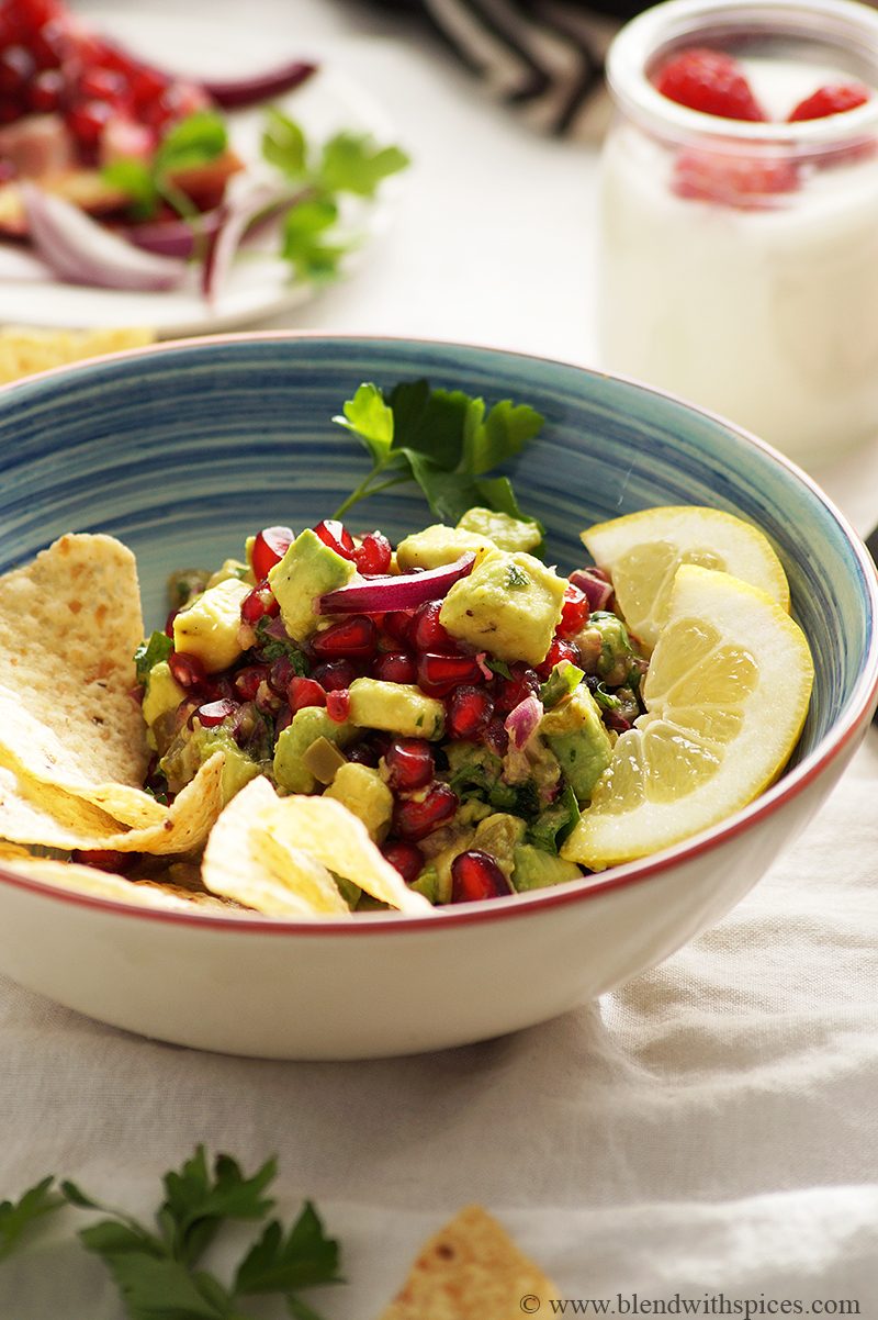 pomegranate avocado salsa served with nachos and lemon slices on a blue bowl