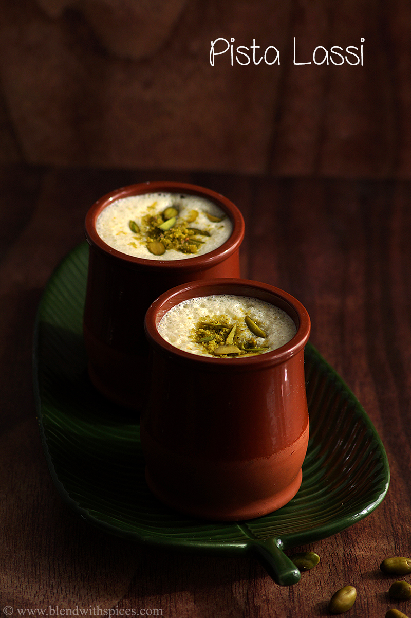 A sweet pista cardamom lassi served in two terracotta tumblers and garnished with pistachios.