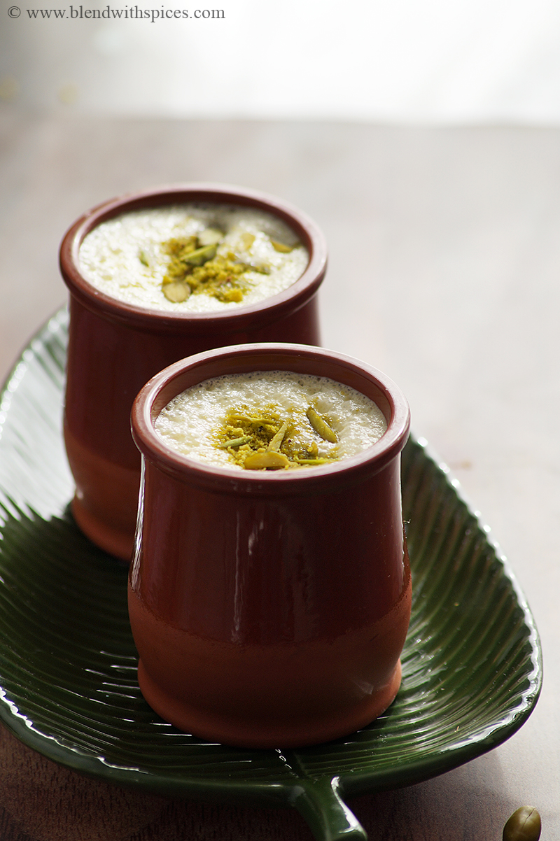 Indian Pista Lassi served in two terracotta tumblers, placed on a green tray and garnished with chopped pistachios