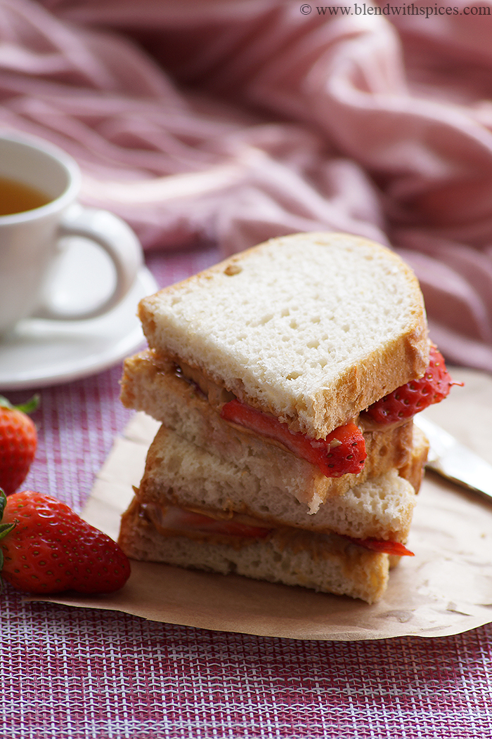 peanut butter strawberry sandwiches are served with a cup of tea.