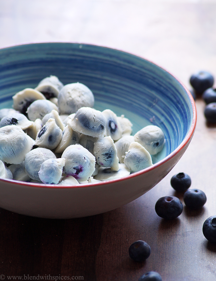 frozen yogurt blueberries are served in a blue bowl
