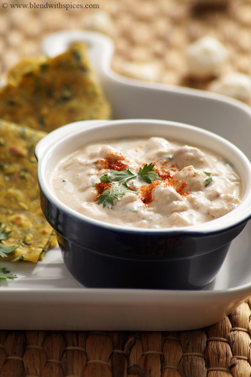 phool makhana raita garnished with cilantro and served with paratha on a white plate