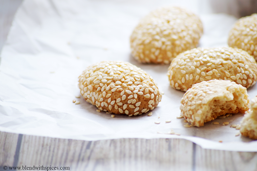 Crispy Italian sesame covered cookies arranged on a parchment paper