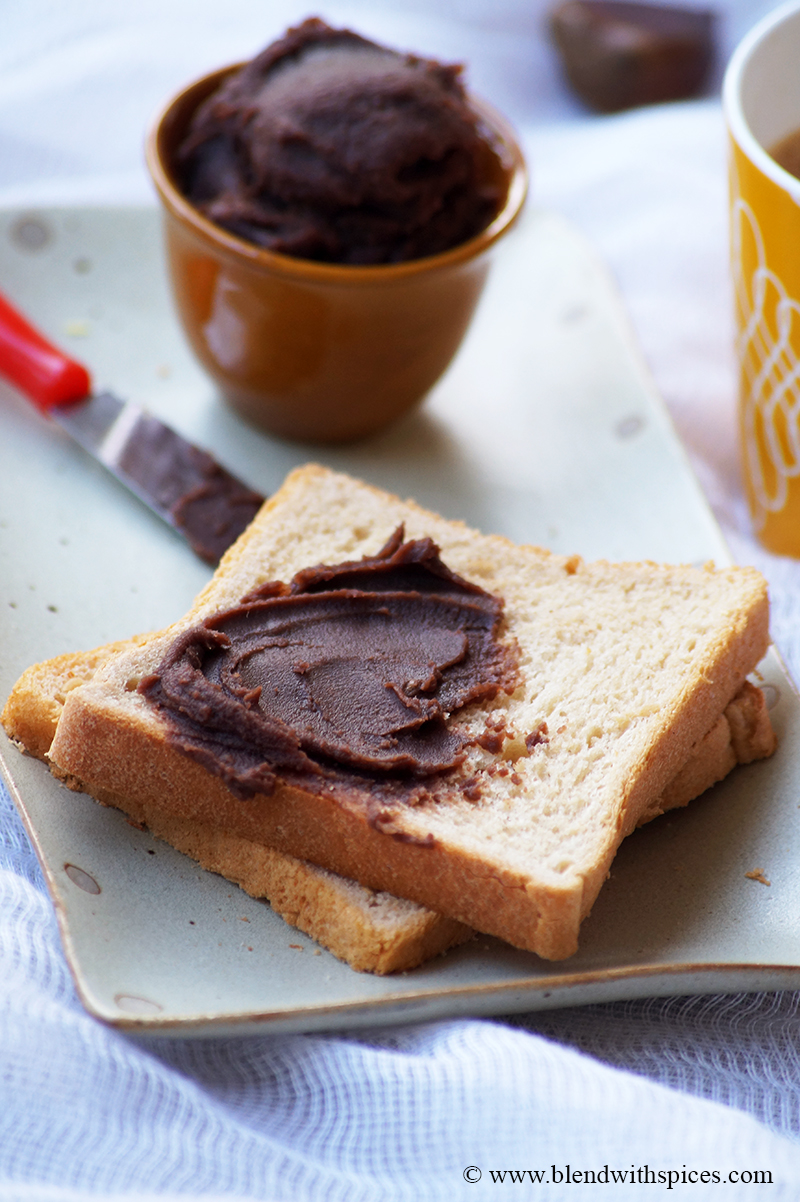 a picture of chestnut spread slathered on a bread slice and served along with coffee in a yellow mug.