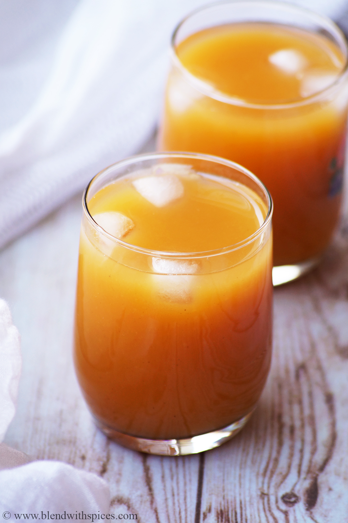 mango drink served in two glasses with ice cubes on a white background