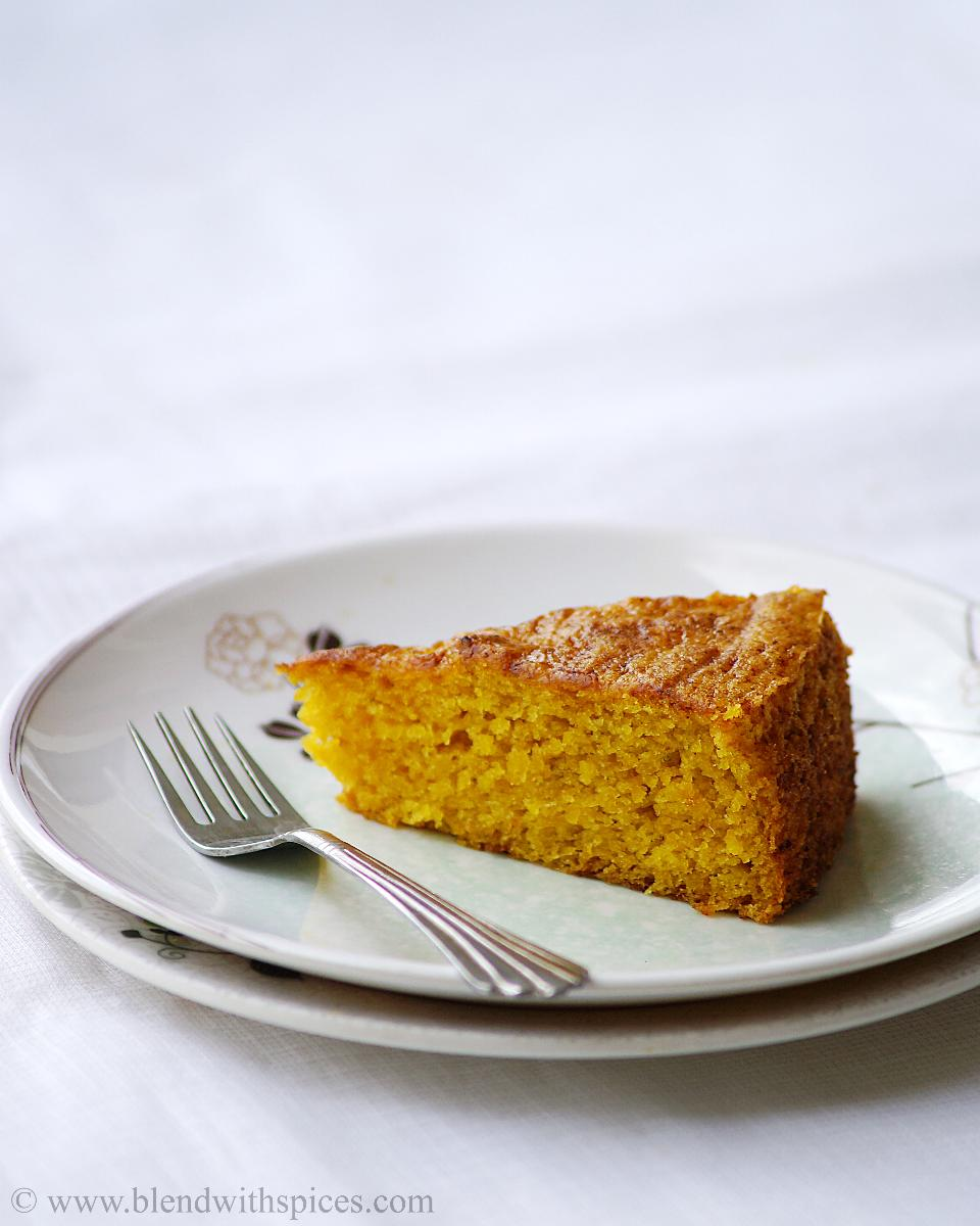 A side view of the moist mango cake served on white plate with a fork