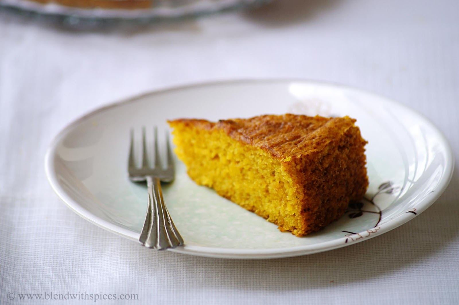 a slice of mango coffee cake with a fork on white background