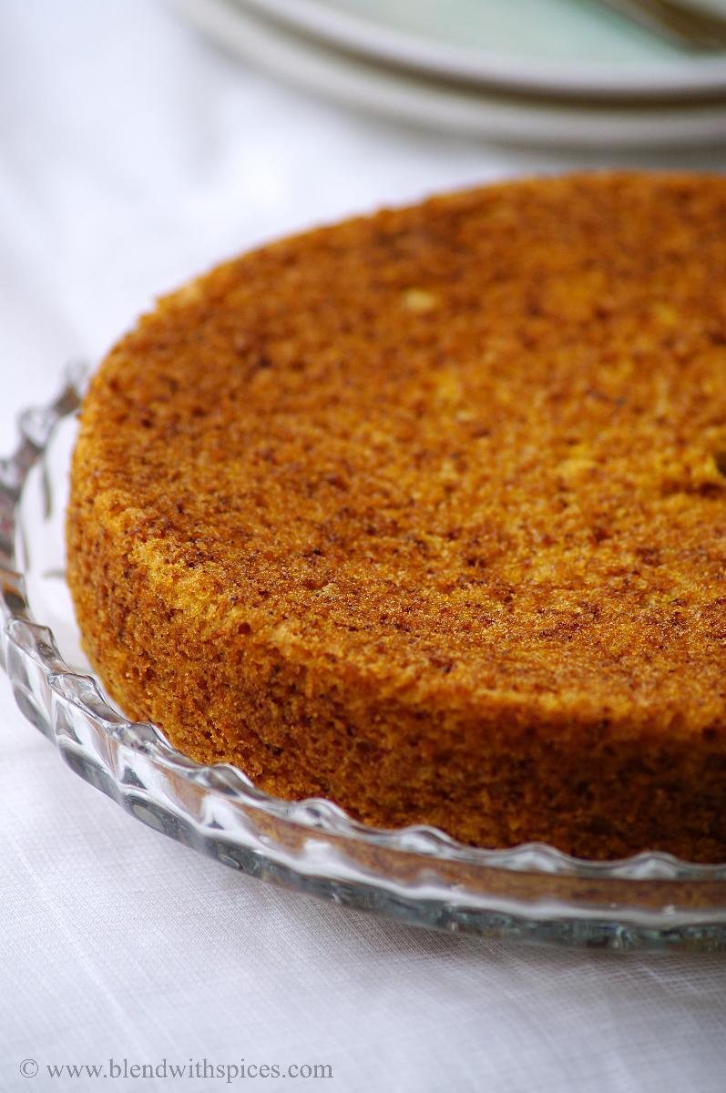 a close-up shot of moist mango cake on a white background