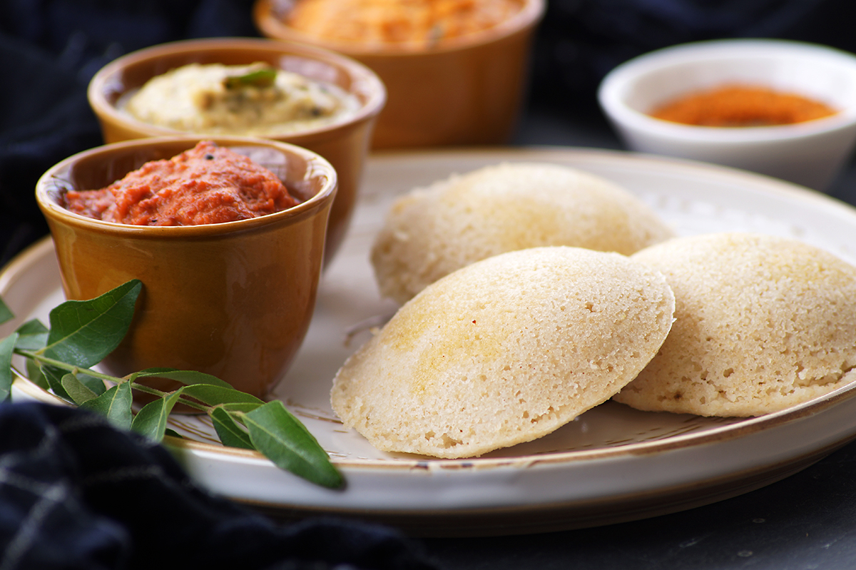 ghee topped instant oats idli served on a white plate along with south indian chutneys