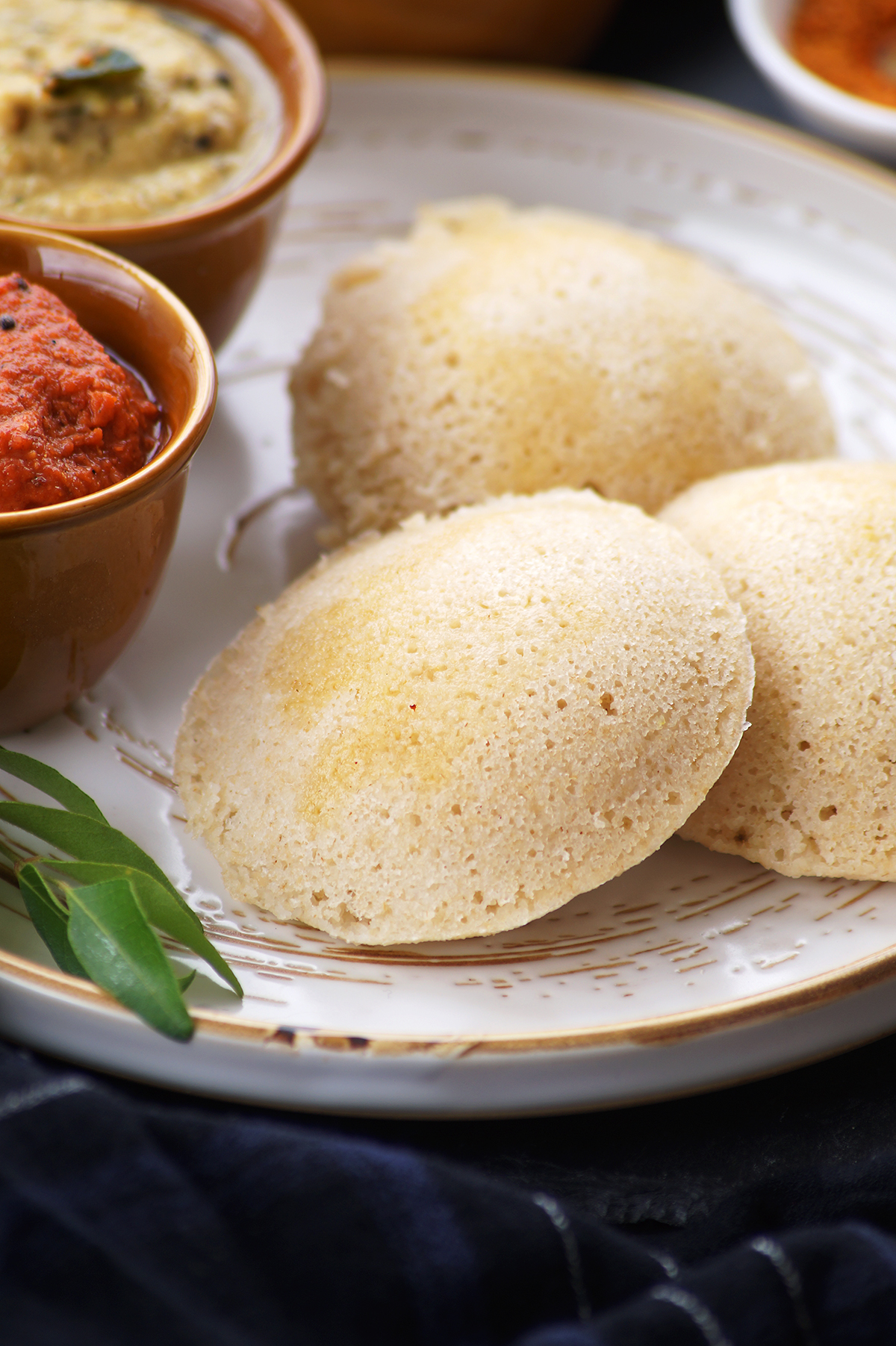 soft south indian oats idli served on a white plate and topped with ghee.